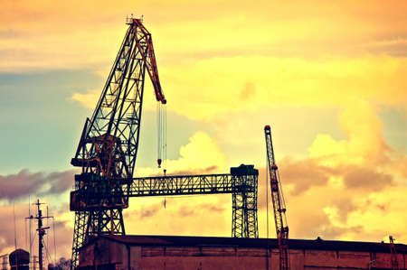 sullen: Industrial conceptual image. Dark and sullen clouds over industrial area with cranes.