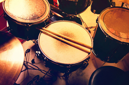drum: Drums conceptual image. Picture of drums and drumsticks lying on snare drum. Retro vintage instagram picture. Stock Photo