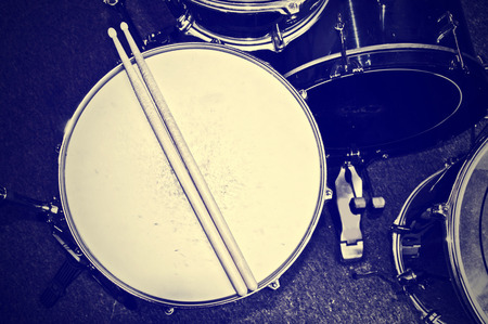 Drums conceptual image. Picture of drums and drumsticks lying on snare drum. Retro vintage instagram picture. 스톡 콘텐츠