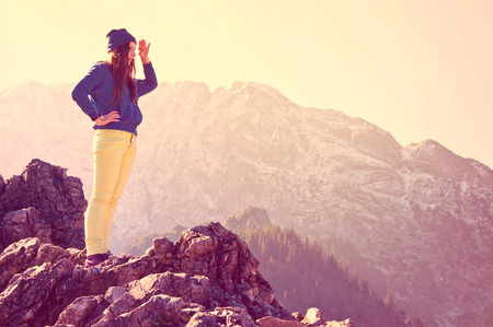 new opportunity: Young beautiful girl standing on the rocks in mountains and looking for new opportunities. Vintage instagram picture. Stock Photo