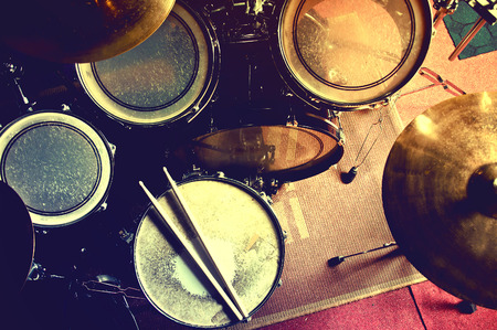 Drums conceptual image. Picture of drums and drumsticks lying on snare drum. Retro vintage instagram picture. Banco de Imagens