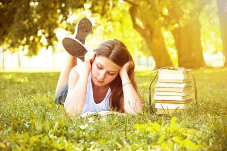 Young beautiful college student girl lying down on the green grass and reading a book at campus at warm day. Education. Back to school conceptual image. Stock Photo