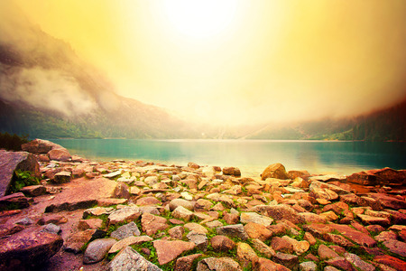 morskie: Fog over lake in mountains. Fantasy and colorfull nature landscape. Nature conceptual image. Morskie Oko in Tatry, Poland. Stock Photo
