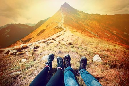 mountain: Tourism in mountains. A couple of tourists rest on the mountain path. Nature in mountains at autumn.