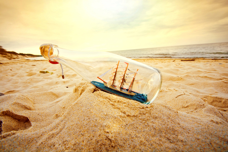 curious: Ship in the bottle lying on the beach. Souvenir conceptual image. Nature in paradise.