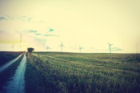 energy picture: Windmills on the field. Alternative ecological energy. Instagram vintage dark picture.