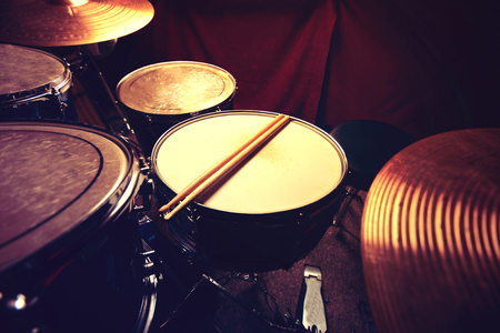 Drums conceptual image. Drums and drumsticks lying on snare drum. Retro vintage instagram picture.