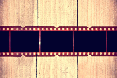 filmstrip: Photographic film on wooden background. Instagram retro vintage picture. Stock Photo
