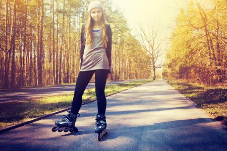 rollerblade: Teenage girl on roller skates at summer. Inline skates sport conceptual image. Instagram vintage picture. Stock Photo