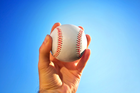 pitcher: Baseball game. Baseball ball holding by hand against blue clean sky.