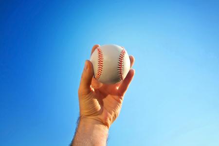 Baseball game. Baseball ball holding by hand against blue clean sky.