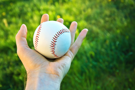 squeeze shape: Baseball game. Baseball ball holding by hand against green fresh grass.