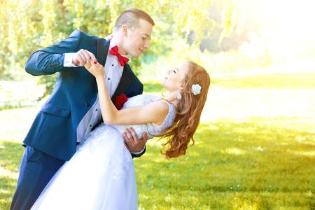 Wedding Couple Tanz im grünen Park im Sommer. Ehe und Hochzeit Konzept Bild.