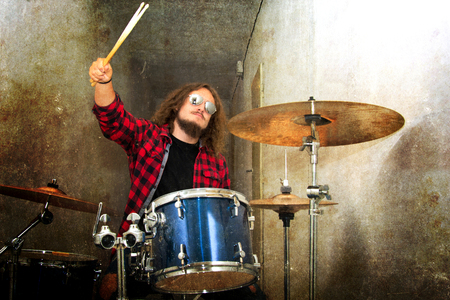 Drums conceptual image. Rock drummer holding drumsticks and playing on drums. Retro vintage grunge picture. Stock Photo