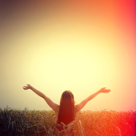 Girl lift her hands to the sky and feel freedom. Happiness and success concept. Instagram sunburst vintage picture. Stock Photo