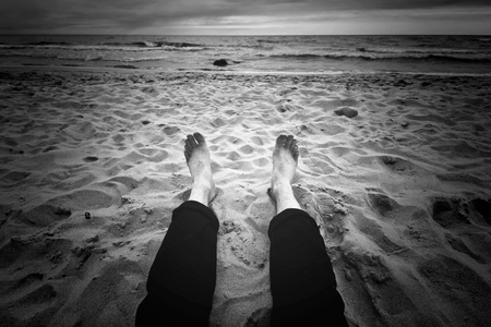 Destination place. Man sitting on the dark beach near ocean. Black and white image. Stock Photo