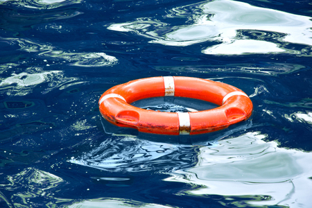 Red lifebuoy in blue water. Safe concept. Stock Photo