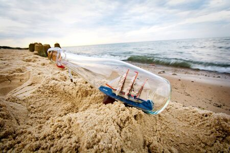 Bottle with ship inside lying on the beach.