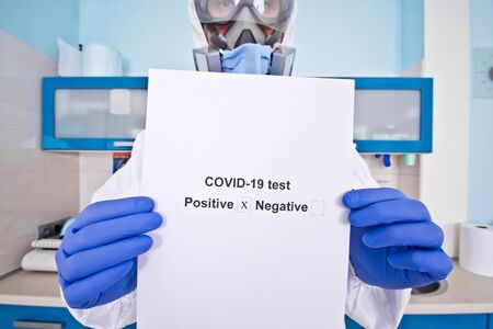 Doctor in protective suit uniform and mask holds coronovirus test results. Coronavirus outbreak. Covid-19 concept.