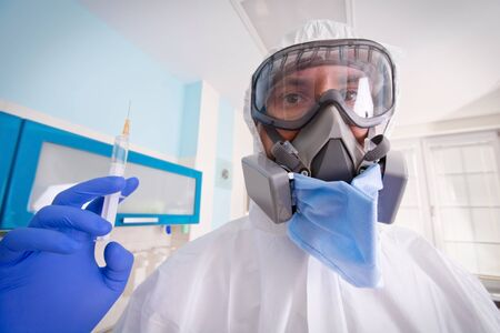 Doctor in protective suit uniform and mask holds injection syringe with vaccine. Coronavirus outbreak. Covid-19 concept.