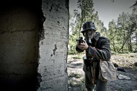 World War 2 Soldier in a gas mask aims his gun. War concept. Reklamní fotografie
