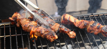 Closeup of meat skewers being grilled in a barbecue