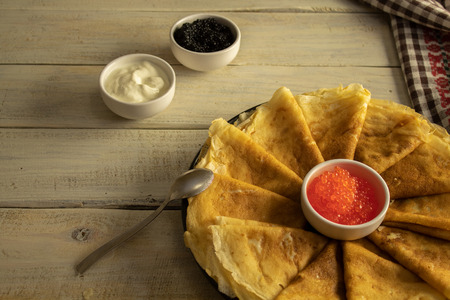 Russian portion of pancakes with red caviar on a wooden texture.