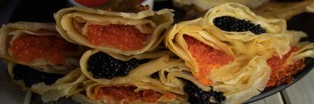 Pancakes stuffed with caviar close-up, mix.