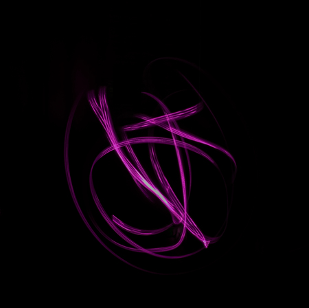 Freeze light photo, abstract streaks pink color on black background, made with light painting or light drawing