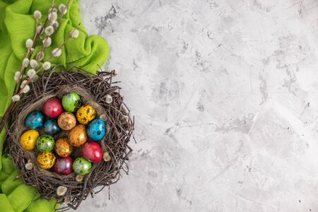 Painted quail eggs for the Easter holiday in a nest with willow branches with a green napkin. On a concrete background. Copy space
