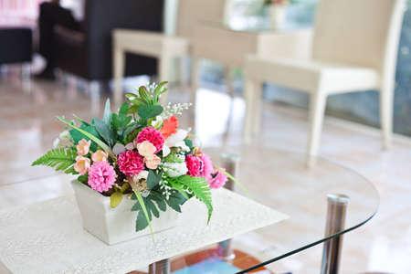 fake flower in vase on table