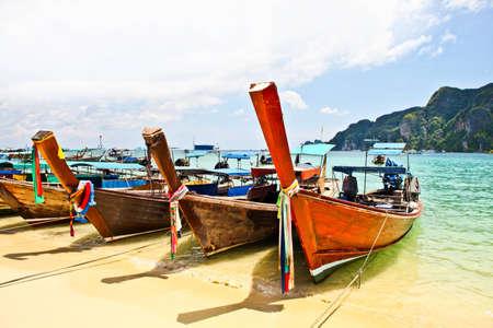 many  thai boats on beach photo