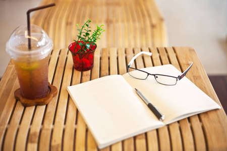coffee notebook glasses and pen on bamboo table