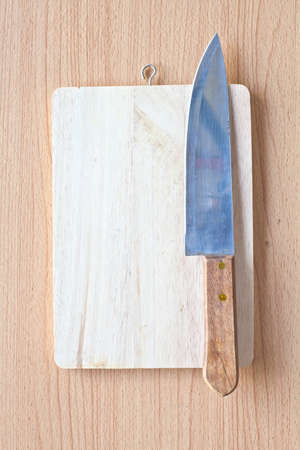 Cutting board on wood background with knife photo