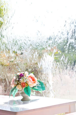 Flower vase on white table with water flow wall