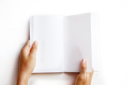two page spread: overhead view of hands holding a blank book ready with copy space ready for text