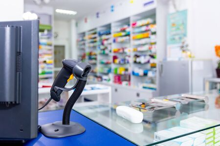 Payment counter with blurred medicines shelves background.