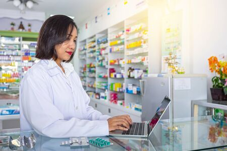Female Pharmacist using the computer at the pharmacy. Medicine, pharmaceutics, health care and people concept.