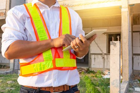 Engineer wears a safety shirt and working with tablet for check Building structure model. Engineering and Architecture concept. Smart working concept.
