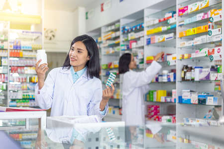Smiling Asian female pharmacist or doctor holding medicine bottle and capsules medicine in clinic or pharmacy.