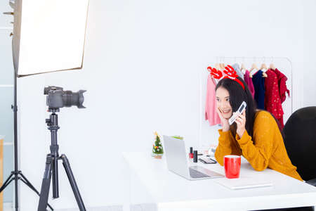 Beautiful asian woman blogger is recording vlog video live streaming about how to make up and use cosmetics. Online shopping and e-commerce concept.