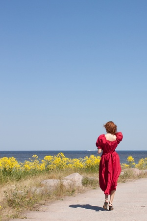 Young lady near the sea in long red dress. Near beauty yellow flowers photo
