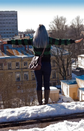 We see woman's back. She's standing on the roof. Stock Photo - 10518381