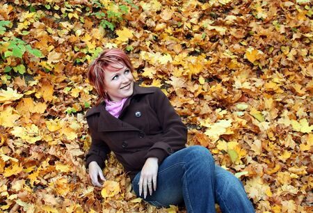 Young pretty woman lies in yellow leaves in park Stock Photo - 10602863