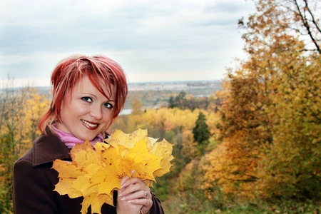 Young pretty woman with yellow leaves in hands Stock Photo - 10602862