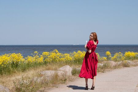 Young lady near the sea in long red dress. Near beauty yellow flowers Stock Photo - 10602864