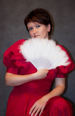 We see pretty Woman in red dress with white fan Stock Photo - 10602874