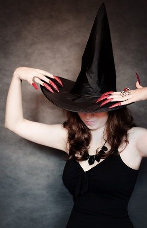 Pretty young witch with black hat and long nails Stock Photo - 10602925