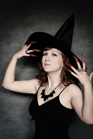 Pretty young witch with black hat and long nails Stock Photo - 10602927