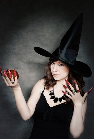 uñas largas: Bastante joven bruja con sombrero negro, uñas largas y la bola de cristal